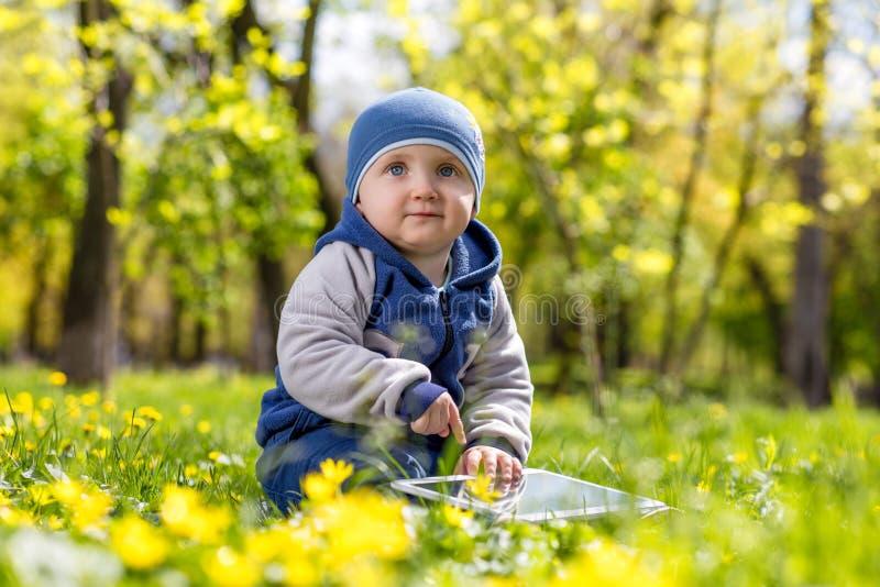 Enfant jouant avec le comprimé en parc images stock
