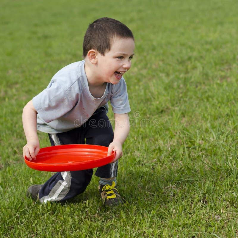 Enfant jouant avec le frisbee image stock