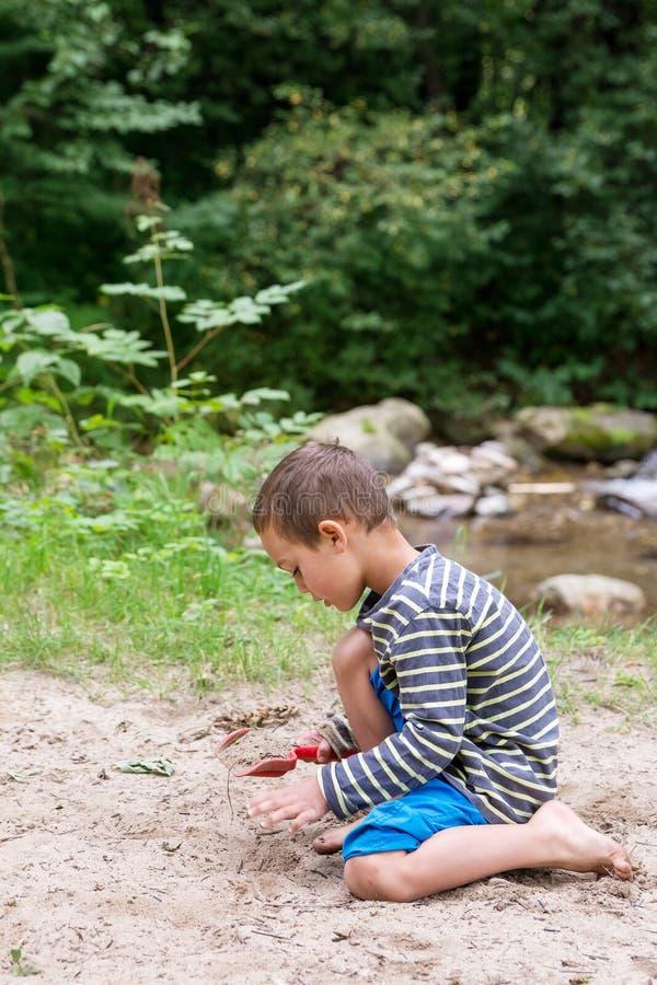 Enfant jouant avec le sable par une rivière photos libres de droits