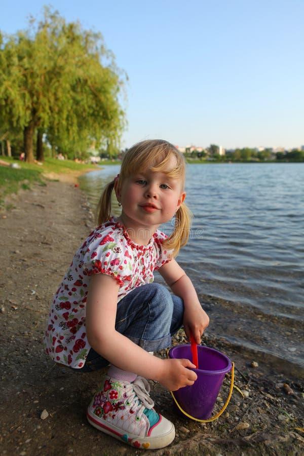 Enfant jouant avec le seau et la pelle photos stock