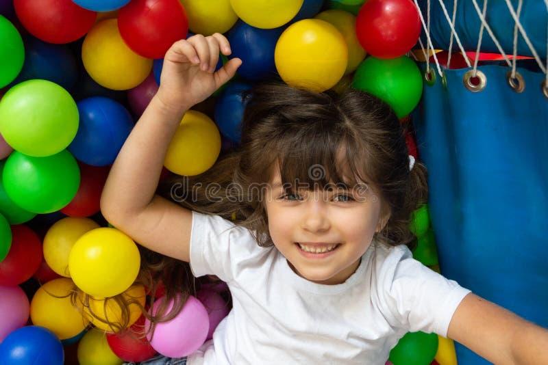 Enfant jouant avec les boules color?es dans la piscine de boule de terrain de jeu Jouets d'activit? pour peu d'enfant Émotion de  photographie stock libre de droits