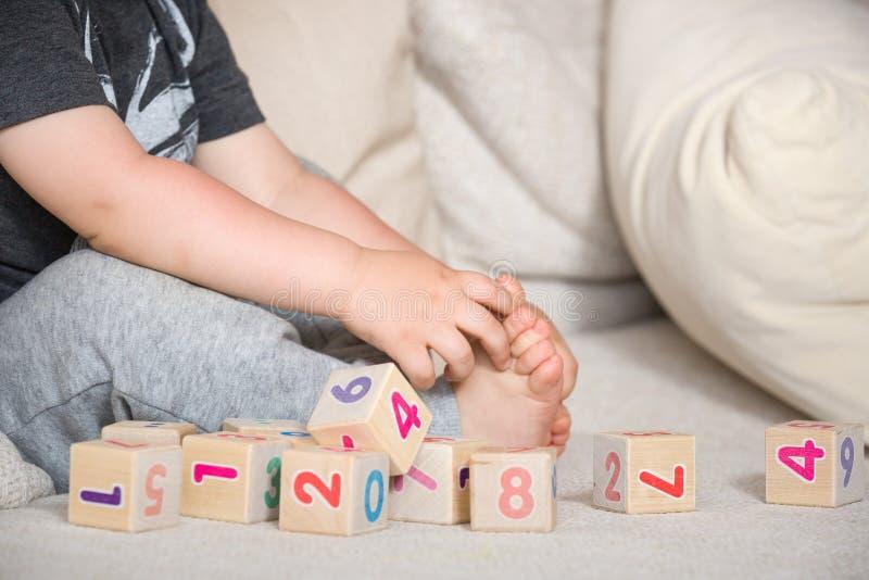 Enfant jouant avec les cubes en bois avec des nombres Enfant en bas âge apprenant des nombres Main d'un enfant prenant des jouets image libre de droits