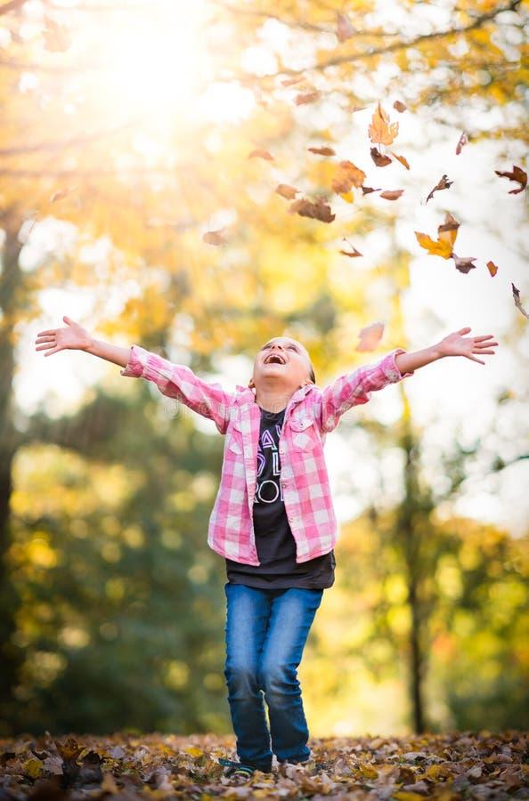 Enfant jouant dans des feuilles d'automne images libres de droits