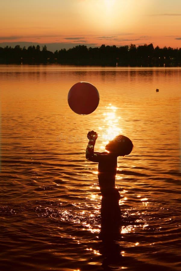 Enfant jouant dans l'eau au coucher du soleil images libres de droits