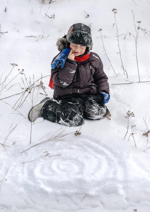 Enfant jouant dans la neige photo stock