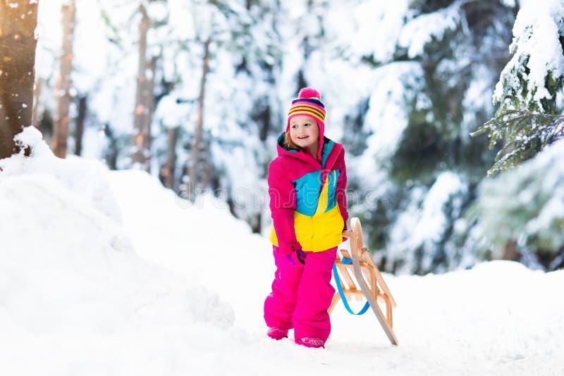 Enfant jouant dans la neige sur le traîneau en parc d'hiver photos stock