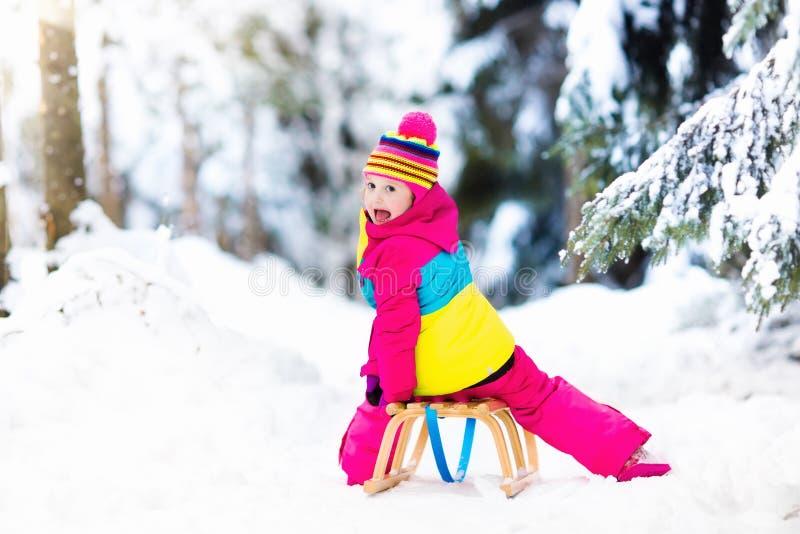 Enfant jouant dans la neige sur le traîneau en parc d'hiver images libres de droits