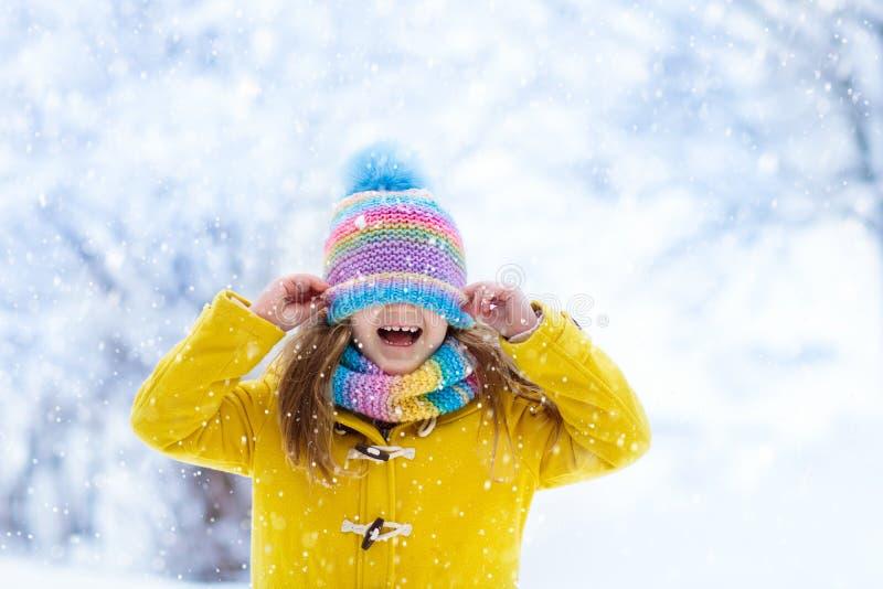 Enfant jouant dans la neige sur Noël Gosses en hiver photo stock