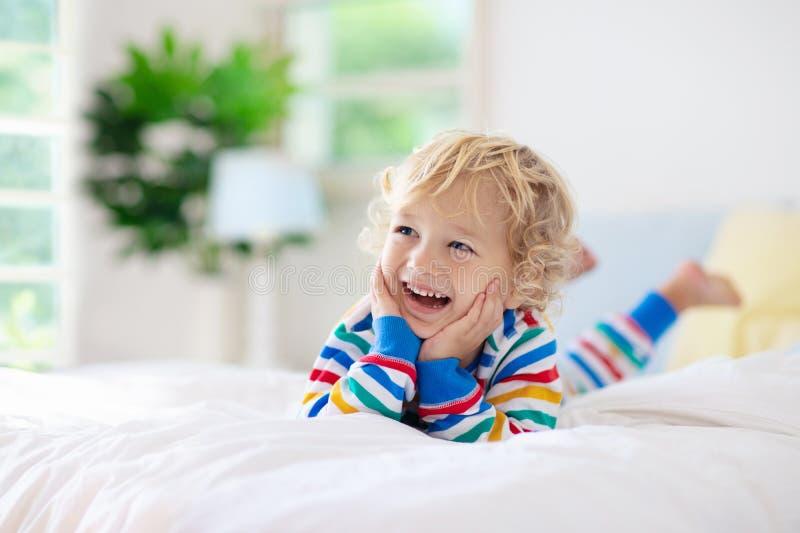 Enfant jouant dans le lit Badine la pièce Bébé garçon à la maison photographie stock