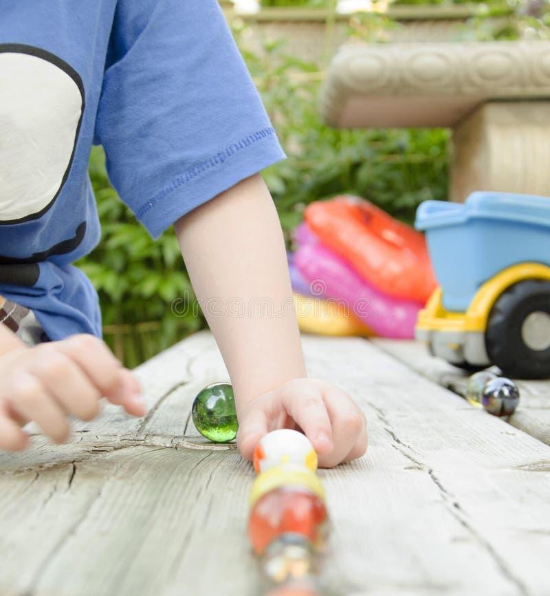 Enfant jouant des marbres photographie stock