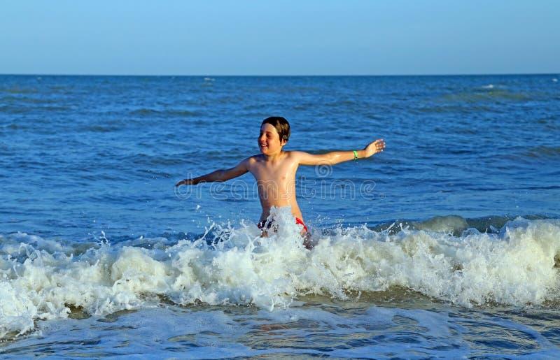 Enfant jouant en mer sautant les vagues de la mer variable image libre de droits