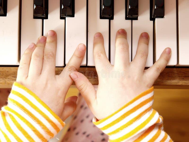 Enfant jouant le piano photos stock
