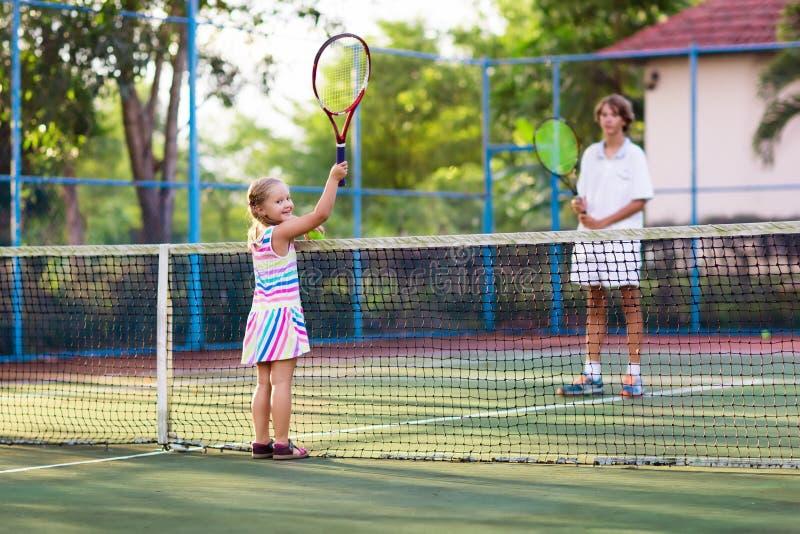 Enfant jouant le tennis sur la cour extérieure photo stock