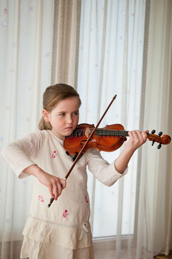 Enfant jouant le violon à la maison photos stock