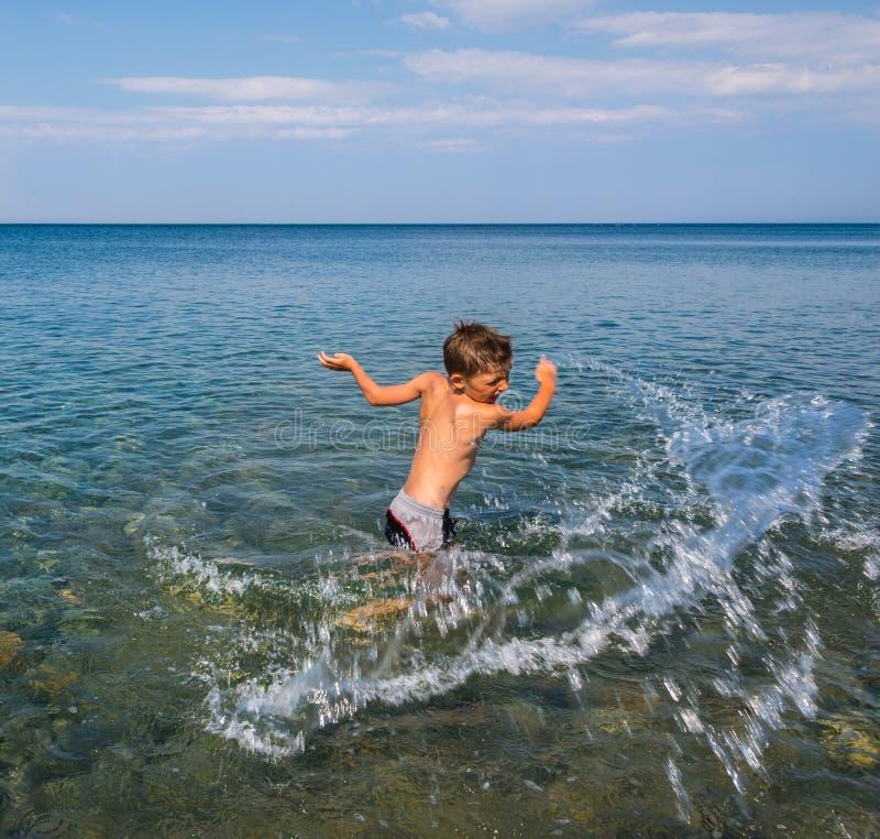 Enfant jouant sur la mer images stock