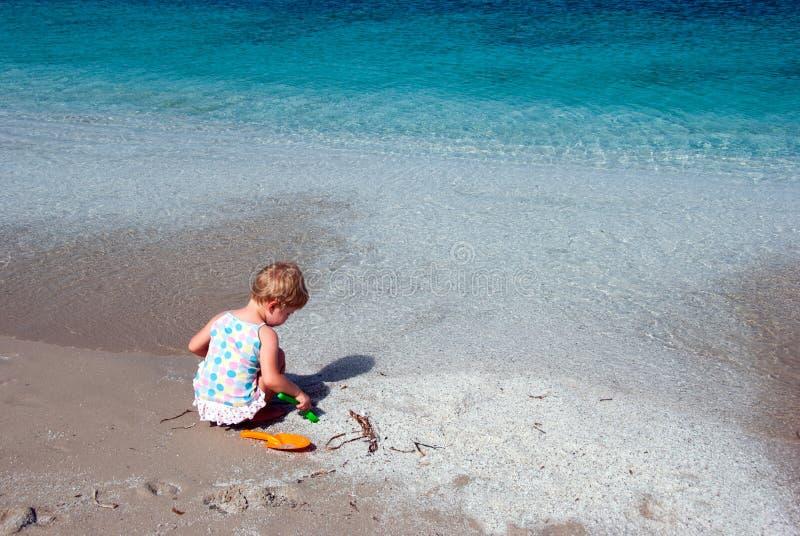 Enfant jouant sur la plage photos stock