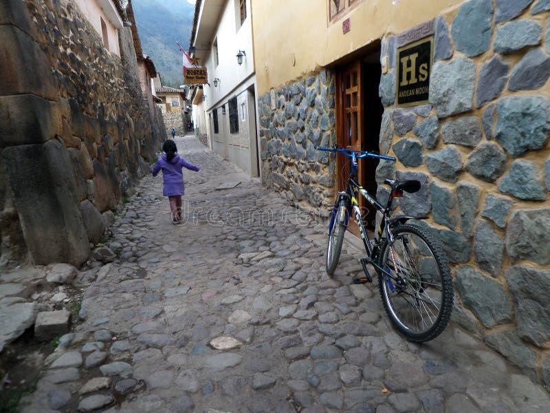 Enfant jouant sur la rue dans Ollantaytambo photographie stock