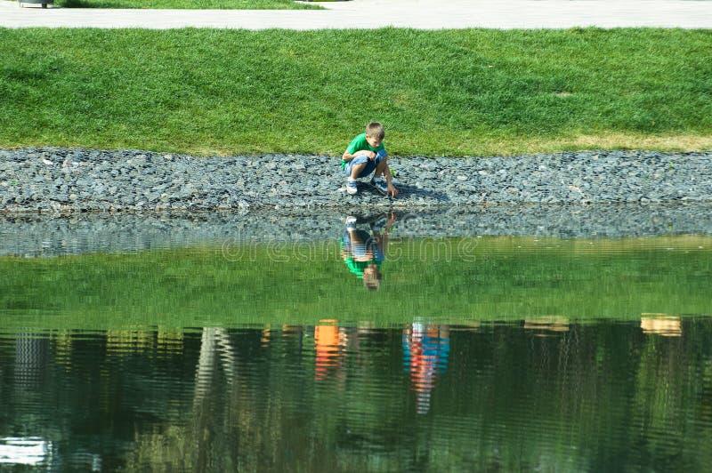 Enfant jouant sur le rivage de lac en parc de Butovo, Moscou, Russie photos stock