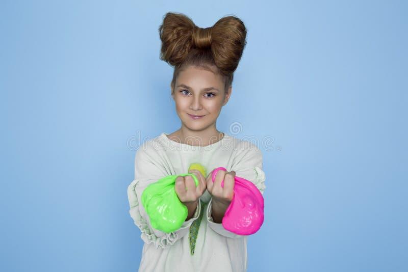 Enfant jouant Toy Called Slime fabriqué à la main, compression de mains d'isolement sur le fond bleu photos stock