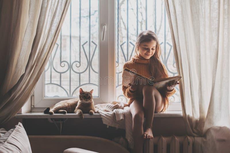 Enfant lisant un livre avec le chat photos stock