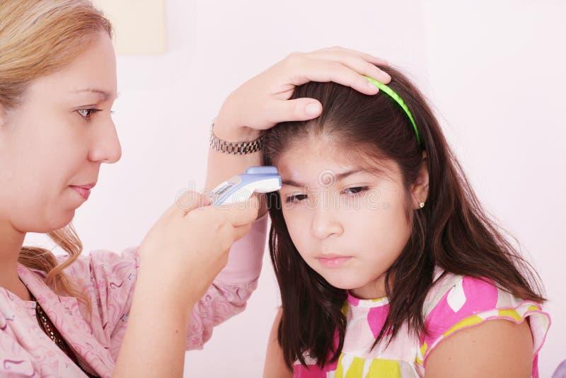 Enfant malade étant contrôlé avec un thermomètre images libres de droits