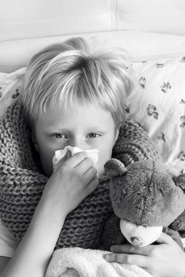 Enfant malade avec l'ours de nounours image stock