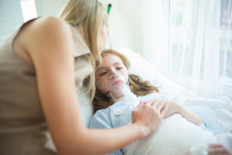 Enfant malade avec le masque à oxygène s'étendant dans le lit au ` d'hôpital et de mère image libre de droits