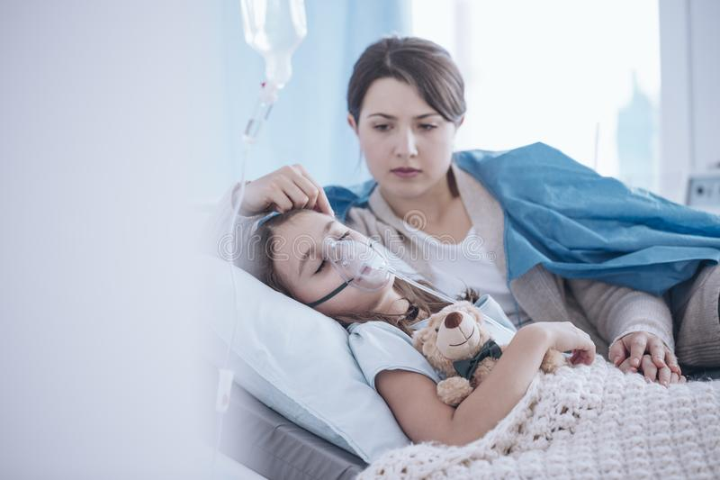 Enfant malade de sommeil de soutien inquiété de mère avec le masque à oxygène et image stock