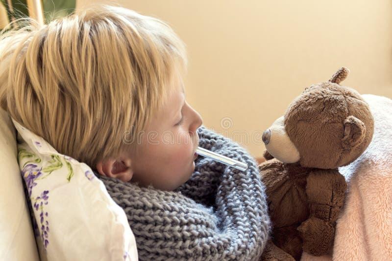 Enfant malade se situant dans le lit photo stock