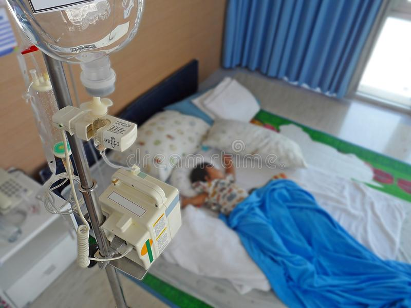 Enfant malade se situant dans un hôpital avec IV photo stock