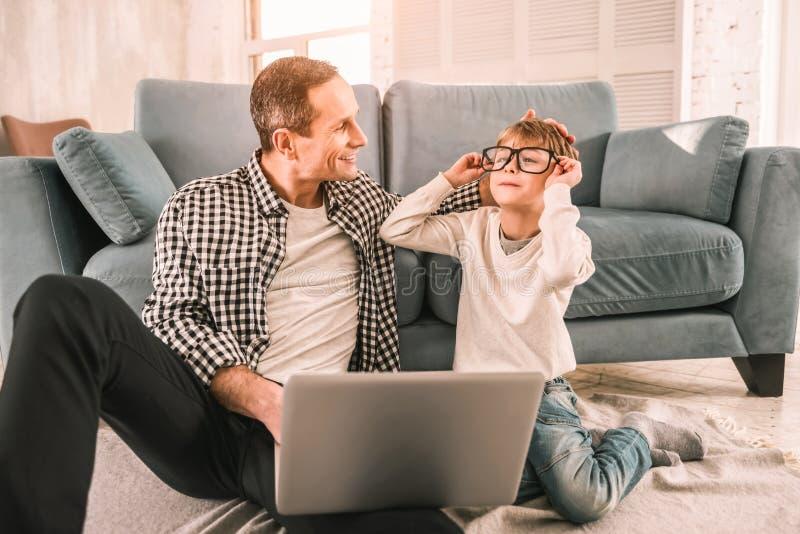Enfant maladroit distrayant son père sérieux du travail photo stock