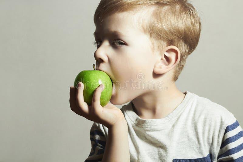 Enfant mangeant Apple Little Boy avec la pomme verte blanc de studio de santé de nourriture de flocons d'avoine de fond macro Fru photographie stock libre de droits