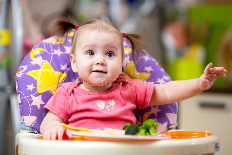 Enfant mangeant de la nourriture sur la cuisine photos libres de droits