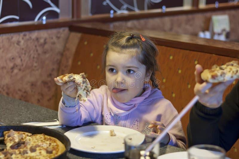 Enfant mangeant de la pizza image stock