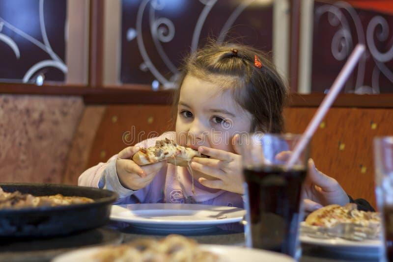 Enfant mangeant de la pizza dans le restaurant image libre de droits