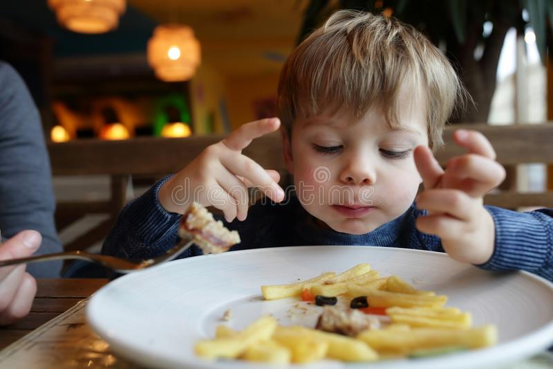 Enfant mangeant des pommes frites photographie stock libre de droits
