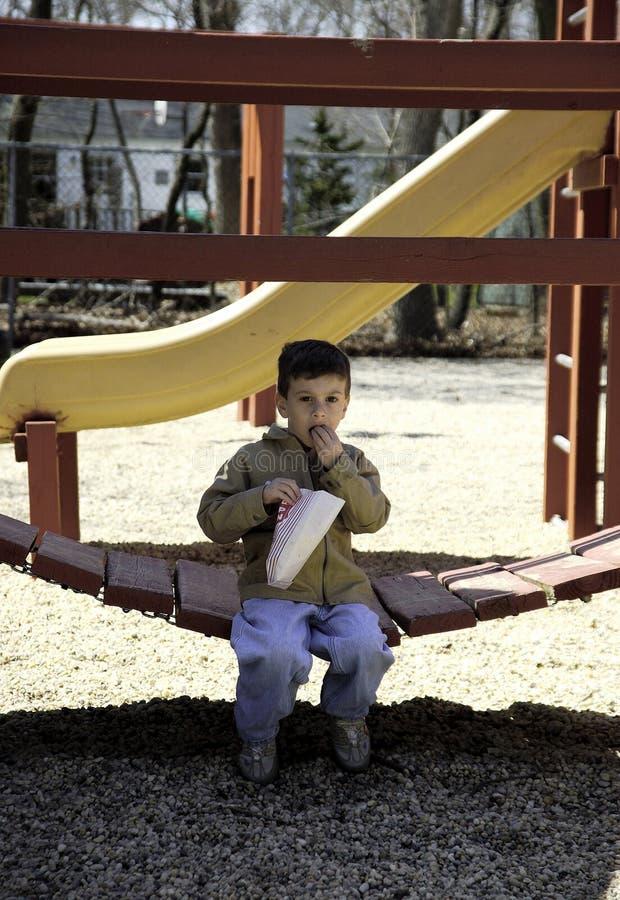 Enfant mangeant du maïs éclaté au stationnement photo stock
