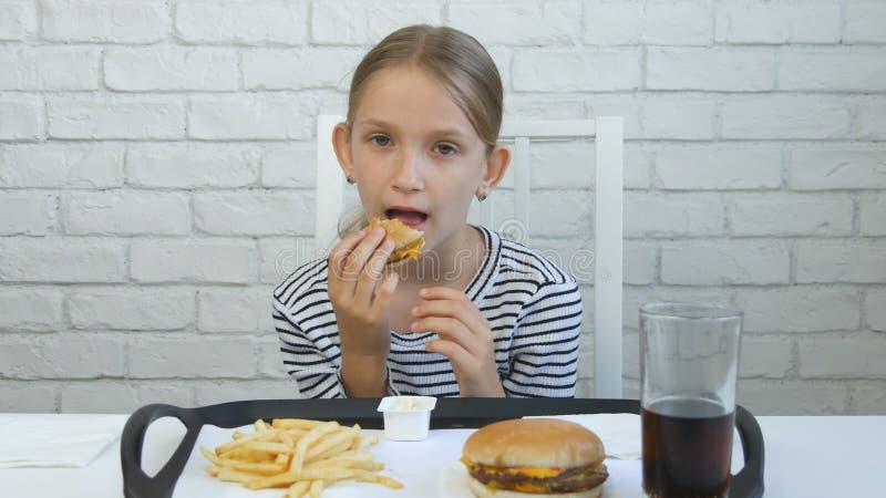 Enfant mangeant l'hamburger en restaurant, enfant et aliments de préparation rapide, jus potable de fille image libre de droits