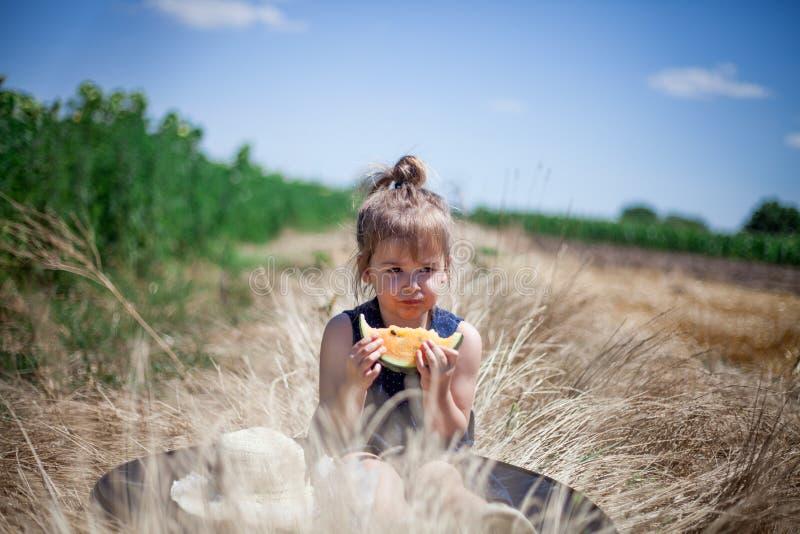 Enfant mangeant la tranche de pastèque jaune dans un pré photo libre de droits