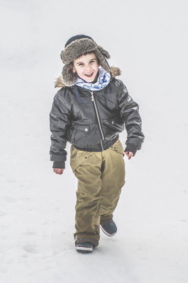 Enfant marchant sur la neige image stock