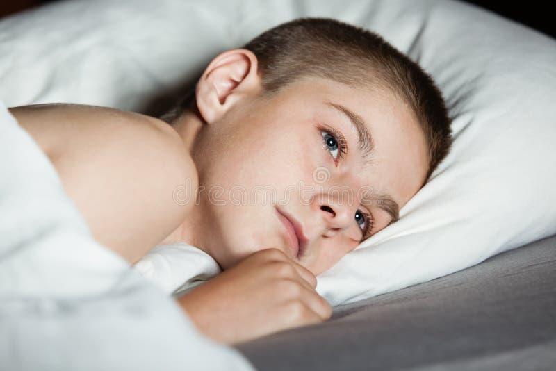 Enfant masculin avec les yeux ouverts fixant sur l'oreiller image stock
