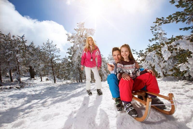 Enfant masculin et féminin s'asseyant sur le traîneau en nature neigeuse photo libre de droits