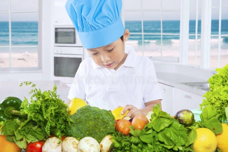 Enfant masculin faisant cuire les légumes sains images stock