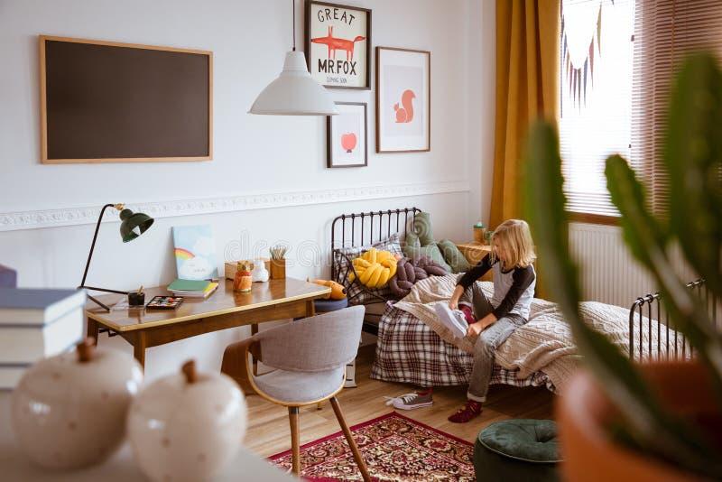Enfant mettant des chaussures dessus dans la chambre à coucher de style de cru photographie stock libre de droits