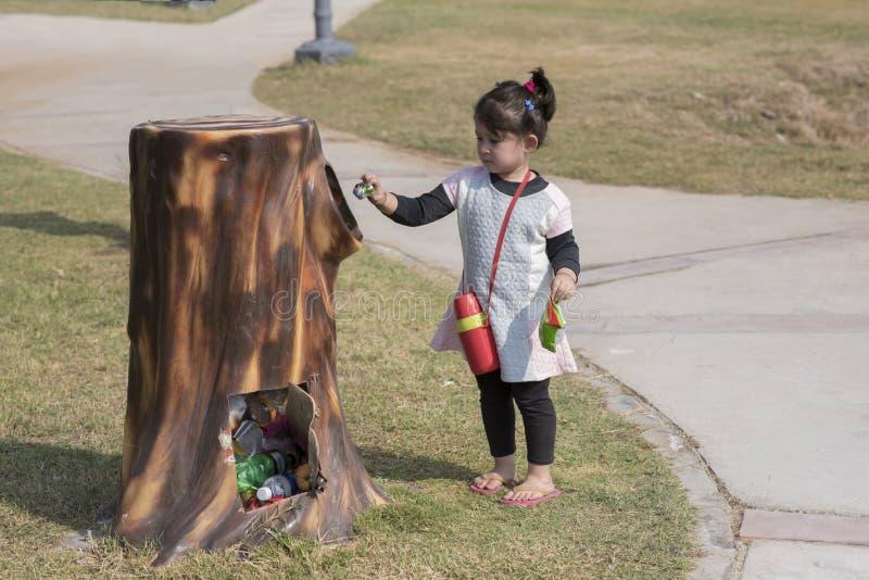 Enfant mettant des déchets dans la poubelle photographie stock