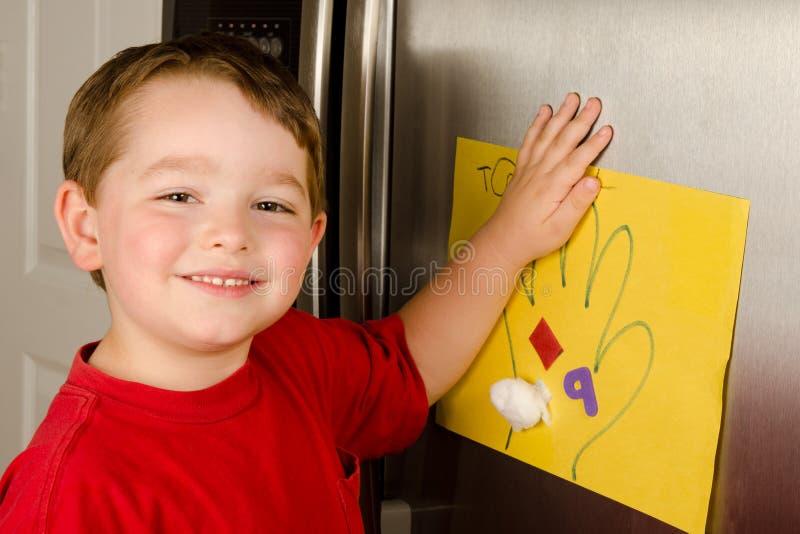 Enfant mettant son art vers le haut sur le réfrigérateur de famille images libres de droits