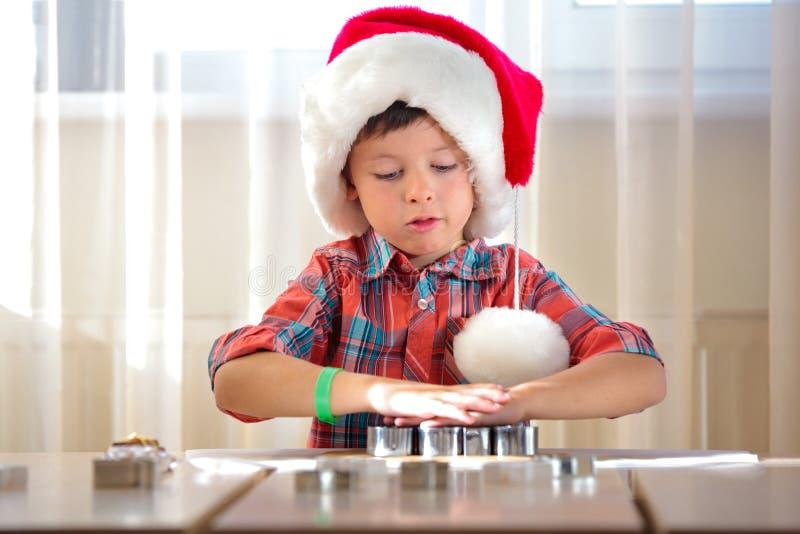 Enfant mignon aidant à la cuisine avec des biscuits de cuisson photo libre de droits