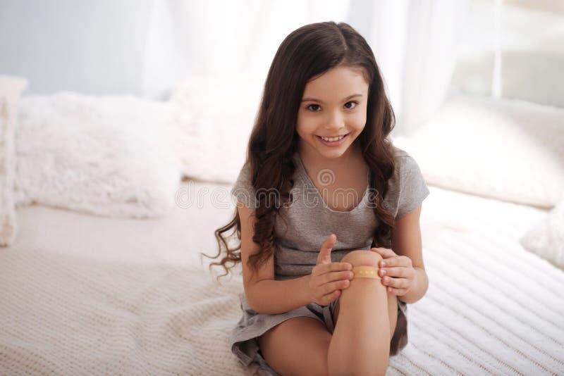 Enfant mignon appliquant l'aide de bande sur la blessure à la maison images stock