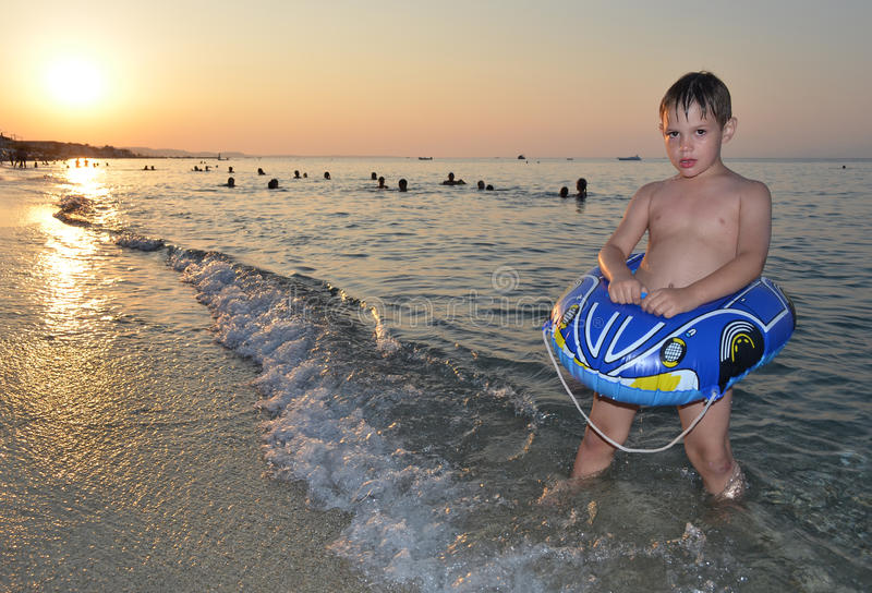 Enfant mignon avec la voiture comme le flotteur sur le coucher du soleil de mer photographie stock libre de droits