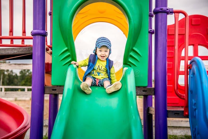 Enfant mignon ayant l'amusement à un terrain de jeu photos stock